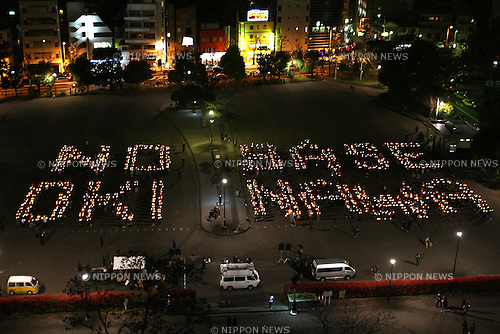 Apr 25, 2010 - Tokyo, Japan - Protesters holding candles form letters reading 'No base Okinawa' during a rally in Tokyo on April 25, 2010. Nearly 1,000 people gathered in Tokyo a day after media reported the central government was moving towards accepting major parts of a 2006 deal to move from the highly populated area of Ginowan in Okinawa to the Marines' Camp Schwab in Nago, also in Okinawa.