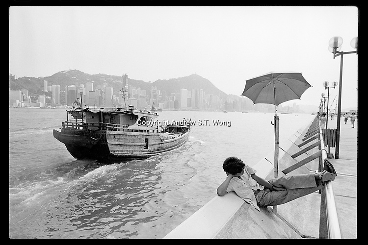 A Hong Kong Chinese man sleeps on the Tsim Sha Tsui East promenade opposite Hong Kong Island as a Chinese fishing boat sails past on a hot Summer day, 1988.