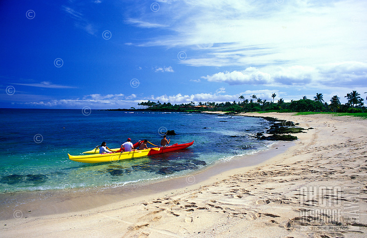 Tourist in an Hawaiian Outrigger Canoe enjoy exploring the waters off scenic Kukio Beach located on the Kona Coast of the Big isle of Hawaii.