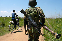 A UPDF soldier walks on a road near Pabbo camp for internally sidplaced people while residents go about thewir lives. THe government army provides protection to formally sanctioned camps for people who have fled their villages in fear of their lives. Kalashnikov AK-47.