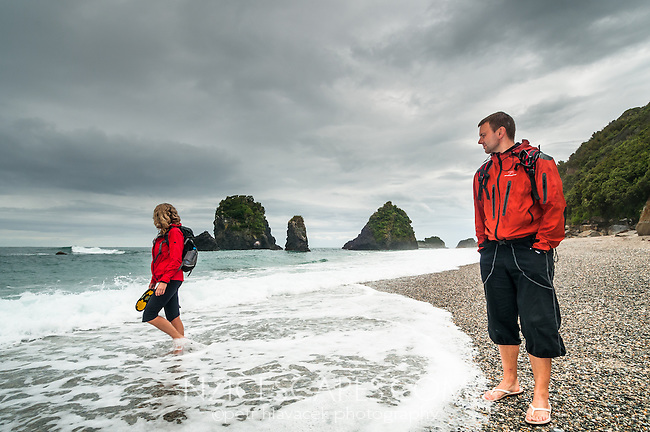 Young couple walking on remote beach in moody weather,  UNESCO World Heritage Area, West Coast, South Westland, New Zealand, NZ