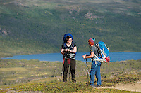 Female hikers take break with lake Abeskojavri - Abiskojaure in background, Kungsleden trail, Lapland, Sweden