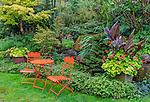 Vashon-Maury Island, WA: Orange patio table and chairs in summer perennial garden.