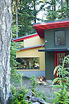 Bright red and yellow make this house stand out from the surrounding trees.