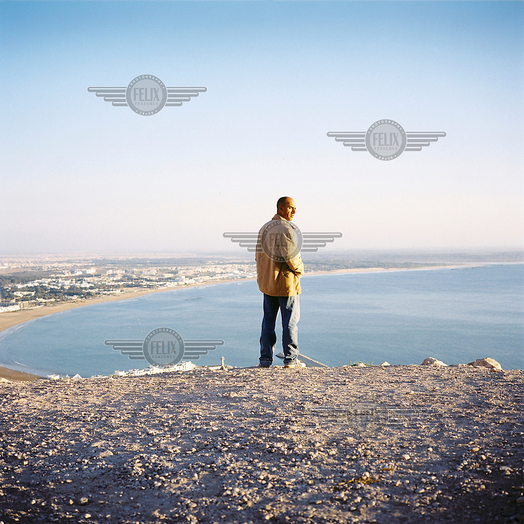 A man looks out over the sea and the town of Agadir.