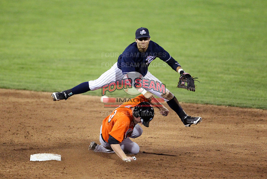 Empire State Yankees shortstop Ramiro Pena #19 turns a double play jumping over Jamie Hoffmann #33 to end the game against the Norfolk Tides in the first ever Triple-A International League game at Dwyer Stadium on April 20, 2012 in Batavia, New York.  Empire State defeated Norfolk 6-4.  (Mike Janes/Four Seam Images)