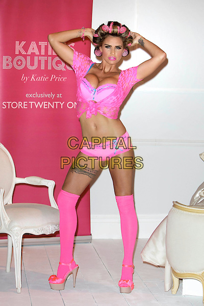 Katie Price (Jordan).The launch photocall for Katie Price's new summer lingerie range for Store 21, The Worx, London, England..May 29th, 2012.full length pink lace top knotted bra cleavage belly stomach midriff knickers underwear tattoo tights stockings garter beige platform sandals shoes rollers curlers in hair hands arms in air.CAP/PP/BK.©Cliff Bass/PP/Capital Pictures.