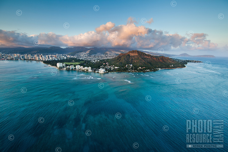 An ultra-wide aerial image taken at sunset of Diamond Head and surrounding East O'ahu, with clear blue ocean and reefs in the foreground.