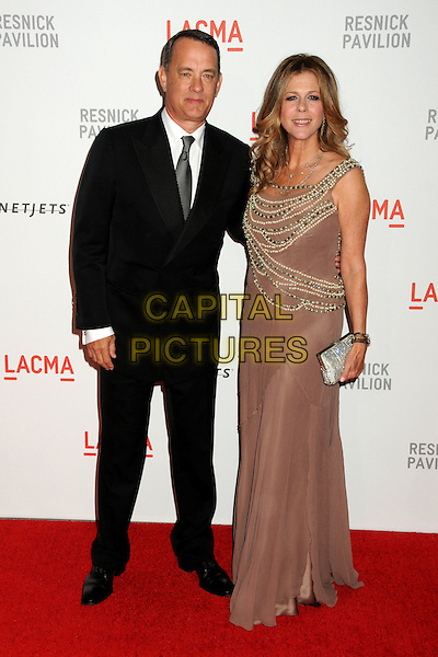 "TOM HANKS & RITA WILSON .LACMA's ""The Unmasking"" of the Lynda & Stewart Resnick Exhibition Pavilion Opening Gala held at the Los Angeles County Museum of Art, - Los Angeles, California, USA, 25th September 2010..full length black suit tie beige brown beaded gold embellished dress clutch bag married husband wife couple silver long maxi.CAP/ADM/BP.©Byron Purvis/AdMedia/Capital Pictures."