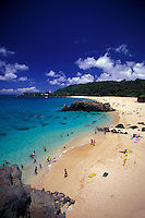 Waimea bay and beach park with people swimming in the clear blue water