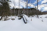 The bridge at North Fork Junction covered in snow during the winter months. This bridge spans the East Branch of the Pemigewasset River along the Thoreau Falls Trail in the Pemigewasset Wilderness of New Hampshire.