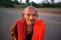January 6th, 2009_KOH KONG, CAMBODIA_ An elderly monk makes his way along a stretch of highway in Cambodia's Koh Kong province.  Koh Kong is in the south west of Cambodia and boarders Thailand.  Photographer: Daniel J. Groshong/Tayo Photo Group