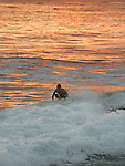 A surfer enjoys the high waves and shallow break off the point of Magic Island in a Oahu, Honolulu, Hawaii.