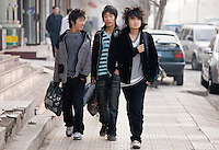 Chinese teenagers walk down a street in Xian, China