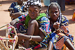 A girl sells woven calabash holders in the weekly market of Djibo in northern Burkina Faso.