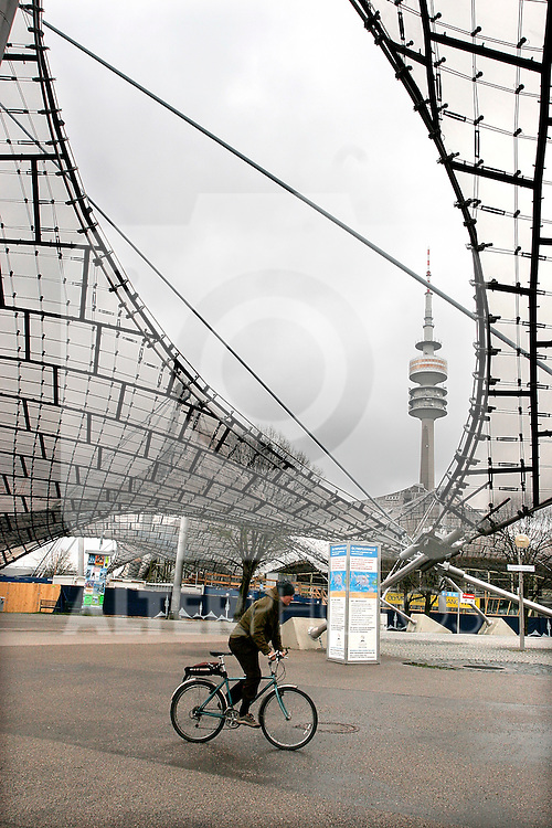 A cyclist rides at the Olympia park with the Olympiaturm or Olympic tower in Munich, April 03, 2008. (ALTERPHOTOS/Alvaro Hernandez)