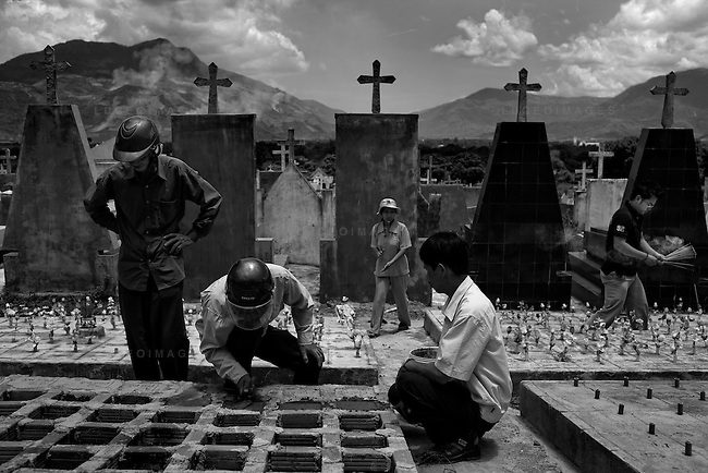 """Catholic church members bury four aborted babies outside of Nha Trang. Vietnam has one of the highest abortion rates in the world. Vietnamese migrate to the fetus cemeteries through out the country saying, """"Xin loi con - I'm sorry child""""."""