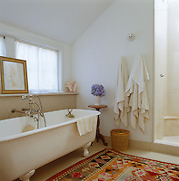 A drawing in a gold frame rests on the window ledge above the roll-topped bath in this bathroom
