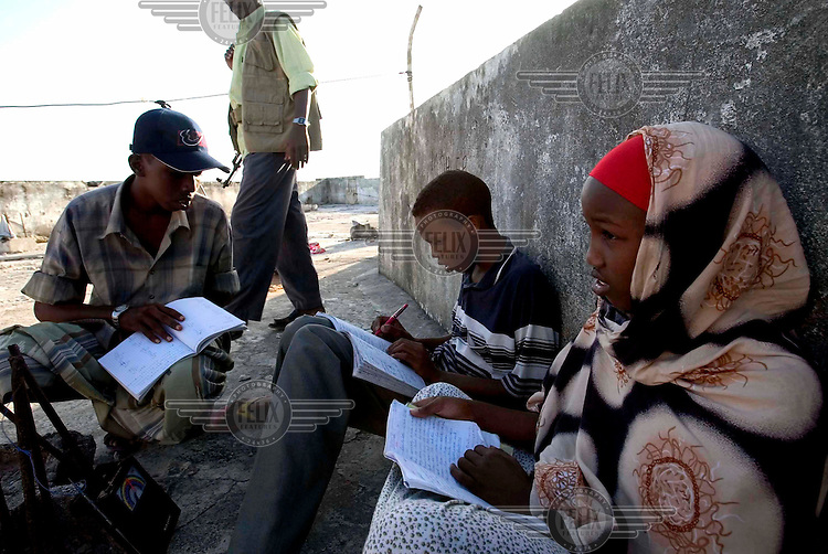 Three young students doing their homework on a rooftop, with an armed man passing by.