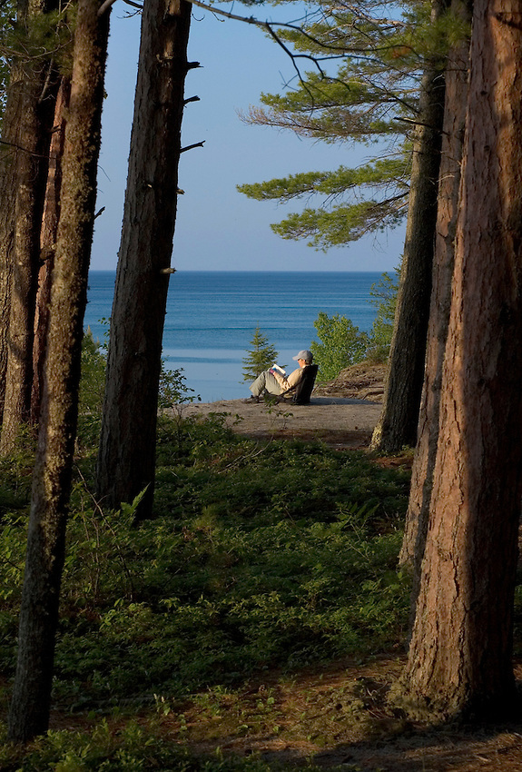 A woman reads a book beneath a stand of red pines at Chapel Beach in Pictured Rocks National Lakeshore near Munising, Michigan.