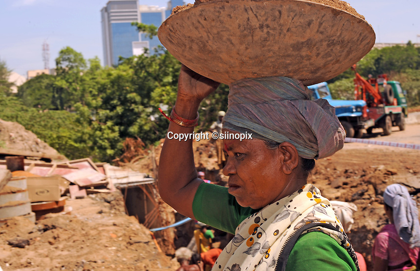 A female worker carries a soil on head at the construction site in Madras, India