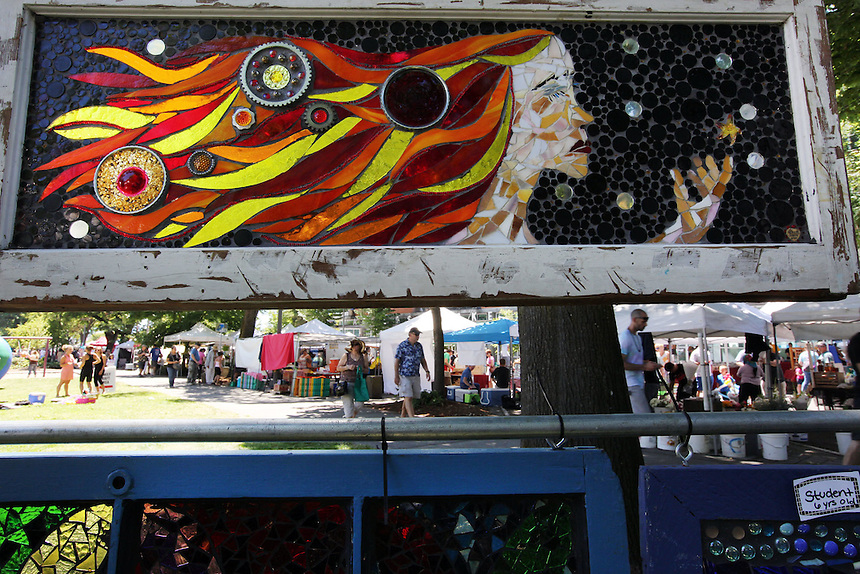 The sunday market is seen beneath a stain glass artwork at the annual Recycled Art Fair in Esther Short Park in downtown Vancouver Sunday June 26, 2016. (Photo by Natalie Behring for the Columbian)