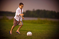 A young boy runs through a field approaching a soccer ball to kick it.
