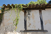 Goias Velho, Brazil. Well preserved colonial town; colonial architecture; old blocked up window, tiled roof with creepers hanging down.