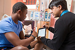 Nirmish Shah, MD, Pediatric Hematology-Oncology Specialist, shows his patient, Clarence Webb, 16, of Fayetteville, how to track his steps, calories and sleep on an app he developed at Duke University Hospital. (Patient release on file)