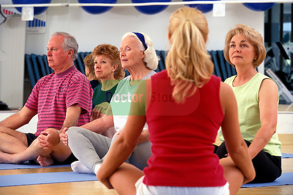 elderly adults enjoying crosslegged relaxation technique in health club studio