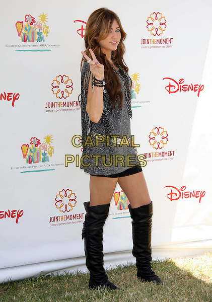 MILEY CYRUS  .Elizabeth Glaser Pediatric AIDS Foundation 20th Annual A Time For Heroes Celebrity Carnival held at Wadsworth Theater, Los Angeles, CA, USA, 6th June, 2009..full length over the knee black knee high boots hand v peace sign silver dress mini belt shorts hotpants tassels bracelet ring .CAP/ADM/KB.©Kevan Brooks/Admedia/Capital Pictures