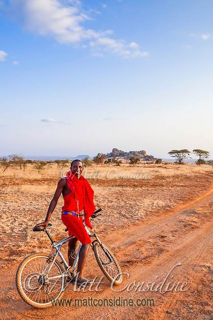 Indigenous male Masai guide in a traditional red robe standing smiling and holding his bicycle on a dirt track on the Kenyan plains, Africa (photo by Wildlife Photographer Matt Considine)