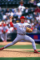 OAKLAND, CA - John Burkett of the Texas Rangers pitches during a game against the Oakland Athletics at the Oakland Coliseum in Oakland, California on July 9, 1998. (Photo by Brad Mangin)