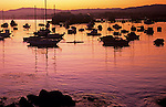 Sunrise with silhouetted sailboats with man in canoe Monterey Bay California USA