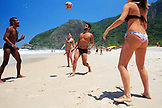 BRAZIL, Rio de Janiero, a group of friends juggle a soccer ball on Prainha Beach