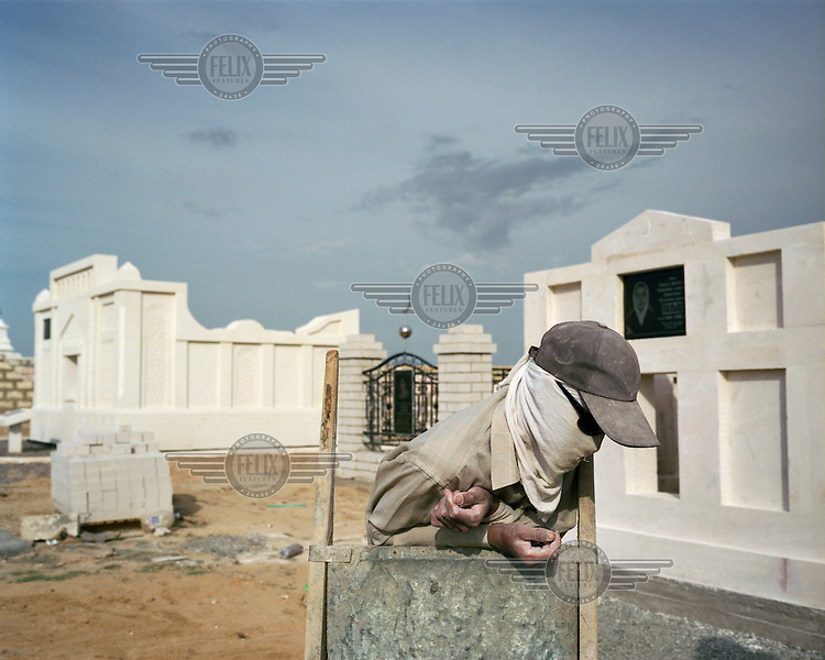 In a coastal cemetery, Uzbek migrant workers wear makeshift masks and sunglasses to protect themselves from the sun's glare, which bounces off the mussel-chalk they work with. They are building elaborate mausoleums for the newly rich middle class. These grave builders work from dawn til dusk, sleeping on site for months at a time.