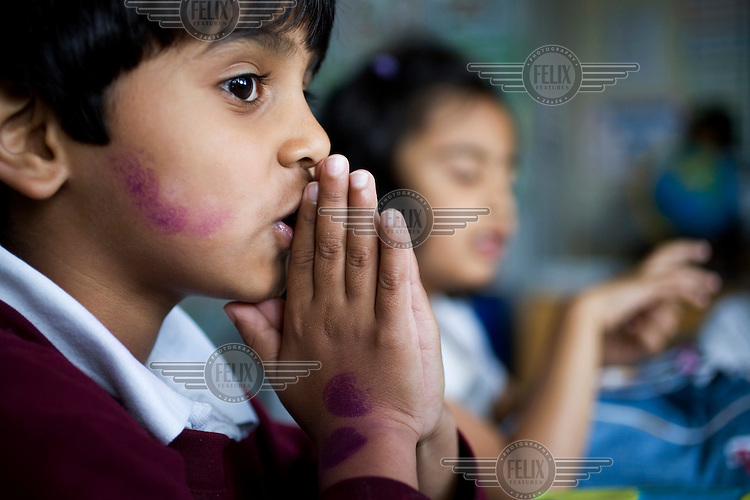 A pupil who has been awarded several 'Good Work' ink stamps at the Krishna-Avanti primary school in Harrow, North London, the first state-funded Hindu faith school in Britain..