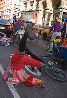New York, NY 15 March 2008 - BIKE LANE LIBERATION CLOWN RIDE - Bike Activist does a shoulder spin as the  troop of cyclists dressed like clowns, warn drivers illegally parked in Manhattan's bike lanes.  Included are several re-purposed, or recycled, DKNY advertising bikes.