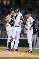 Charlotte Knights pitching coach Richard Dotson (34) has a chat on the mound with relief pitcher Matt Lollis (46) and catcher Vinny Rottino (4) during the game against the Pawtucket Red Sox at BB&T BallPark on July 6, 2016 in Charlotte, North Carolina.  The Knights defeated the Red Sox 8-6.  (Brian Westerholt/Four Seam Images)