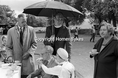 Village church fete in the rain,  Cirencester Gloucestershire England 1974. Woman feeds her husband a Danish paistry.