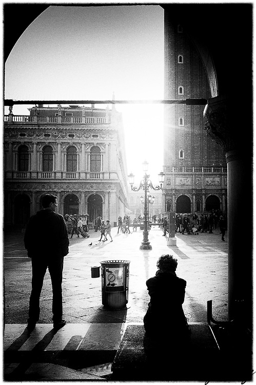 Two people waiting in Piazza San Marco, Venice, Italy.