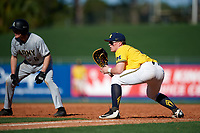 Michigan Wolverines first baseman Jesse Franklin (7) holds Trey Martin (6) on during a game against Army West Point on February 17, 2018 at Tradition Field in St. Lucie, Florida.  Army defeated Michigan 4-3.  (Mike Janes/Four Seam Images)