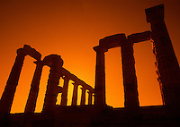 The columns of the ancient Greek ruins of the Temple of Poseidon in silhouette at sunset. Poseidon, Greece.