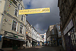 Threatening grey rain clouds over town centre street, Falmouth, Cornwall, England Viking Voyagers advertising banner