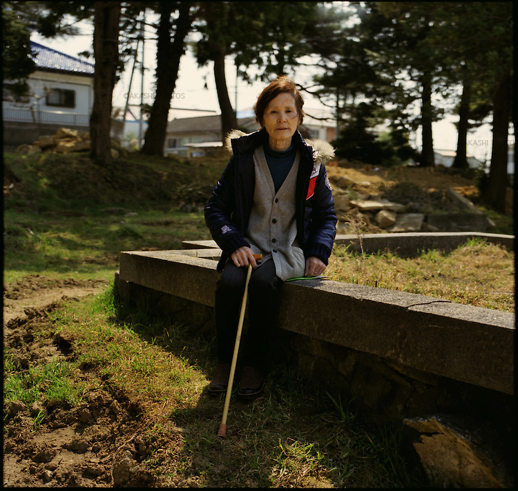 "On May 11, 2011, earthquake of magnitude 9.0 and devastating tsunami hit the Tohoku area, killing more than 15,000 people and missing more than 5,000 people. Mrs. Katsumi Saito, 69, in front of the temporary grave yard for his husband who was washed away by tsunami in front of her. ""He was hangin on to a telephone pole, but after all he was taken away by the tsunami,"" she said. ""He wave his hands to me in the water. I could not help him."""