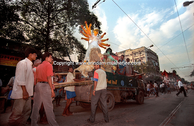 INDIA (West Bengal - Calcutta)  2006, Durga idol being taken to pandals from Kumortuli. Kumortuli in North Calcutta is the hub of Durga idol makers. During the other time of the year the artists engage themselves in prepairing other idols and masks depending on the assignments. But the most of the earning they aquire from making Durga idols. A Durga idol can cost up to 7000 usd. Which is a big price in Indian Currency.  Durga Puja Festival is the biggest festival among bengalies.  As Calcutta is the capital of West Bengal and cultural hub of  the bengali community Durga puja is held with the maximum pomp and vigour. Ritualistic worship, food, drink, new clothes, visiting friends and relatives places and merryment is a part of it. In this festival the hindus worship a ten handed godess riding on a lion armed wth all possible deadly ancient weapons along with her 4 children (Ganesha - God for sucess, Saraswati - Goddess for arts and education, Laxmi - Goddess of wealth and prosperity, Kartikeya - The god of manly hood and beauty). Durga is symbolised as the women power in Indian Mythology.  In Calcutta people from all the religions enjoy these four days of festival in the moth of October. Now the religious festival has become the biggest cultural extravagenza of Calcutta the cultural capital of India. Artistry and craftsmanship can be seen in different sizes and shapes in form of the idol, the interior decor and as well as the pandals erected on the streets, roads and  parks.- Arindam Mukherjee