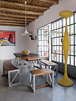 The open plan living and dining area has a modern yet rustic feel with steel and plastic mixed with natural materials and textures. The impressive mahogany and aluminium dining table and benches by Ben Huggins takes pride of place in the room; next to it stands an ETA floor lamp by Kundalini; the painting is by Dan Baldwin.