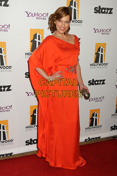 MILLA JOVOVICH.14th Annual Hollywood Awards Gala Presented By Starz held at The Beverly Hilton Hotel, Beverly Hills, CA, USA. .October 25th, 2010 .full length red orange maxi dress clutch bag silver sash waist brooch silk satin grecian one shoulder sleeve hand on hip .CAP/ADM/BP.©Byron Purvis/AdMedia/Capital Pictures