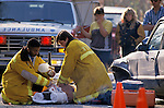 EMTs attending to badly injured victim of car crash on road as concerned eyewitnesses watch, ambulance
