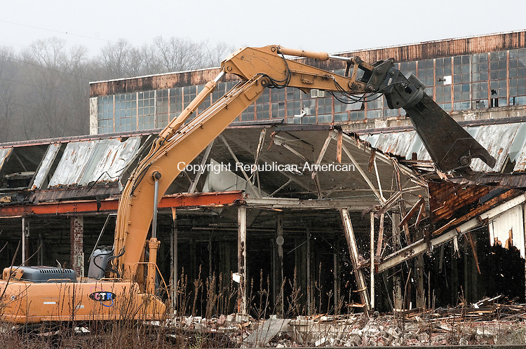 TORRINGTON, CT, 21 APRIL 15 -  An excavator operated by a Connecticut Tank Removal employee begins picking away the former Nidec Building on Franklin Drive in Torrington. The building is being razed.    Alec Johnson/ Republican-American